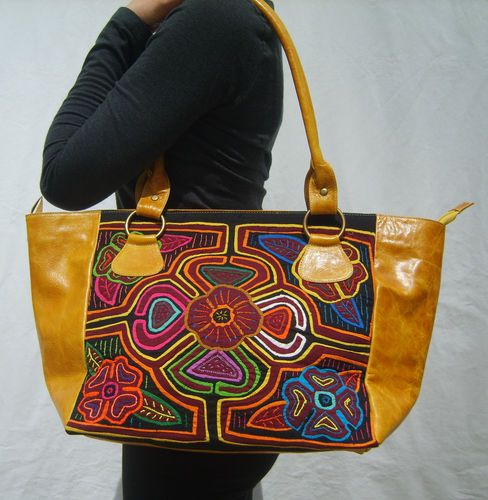 This is a beautiful shoulder bag handmade in Colombia using high quality leather and colorful Mola fabrics sourced from indigenous artisans. Made by the Kuna Indians of northern Colombia, the Mola is a textile art form unique to them and their textiles are incorporated into a variety of wearable art such as shoes, wallets, and purses. These products are made by a family run fair-trade business in Colombia.