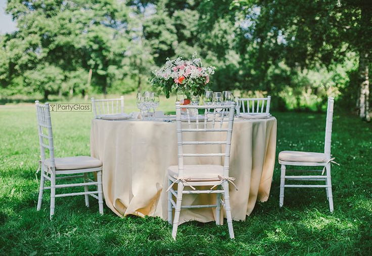 Such a gentle wedding tablescape with white chiavari chairs and soft peach table linens and cushion.