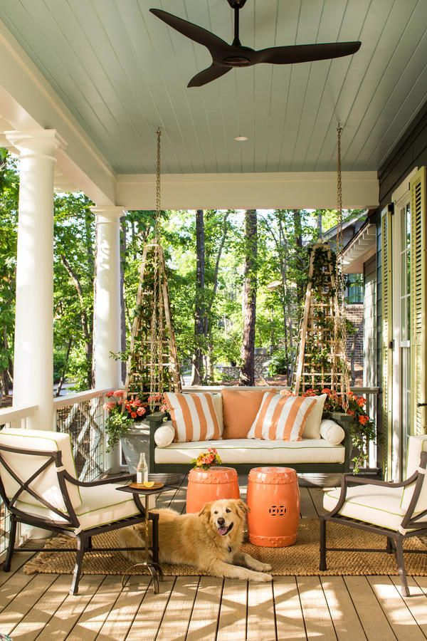 """Perfect Porches - Best Houses of 2016 - Southernliving. """"When we settled on this corner property, it begged for a wraparound porch that faced both streets,"""" said designer Bill Ingram about his Southern raised cottage. """"I think this house could work anywhere. Painted white, it could be in an open field, but here in this rocky locale, we wanted it dark gray. But it still has classic white trim."""" A big hanging bed swing from Ballard Designs anchors the lounging area of this porch perfectly."""