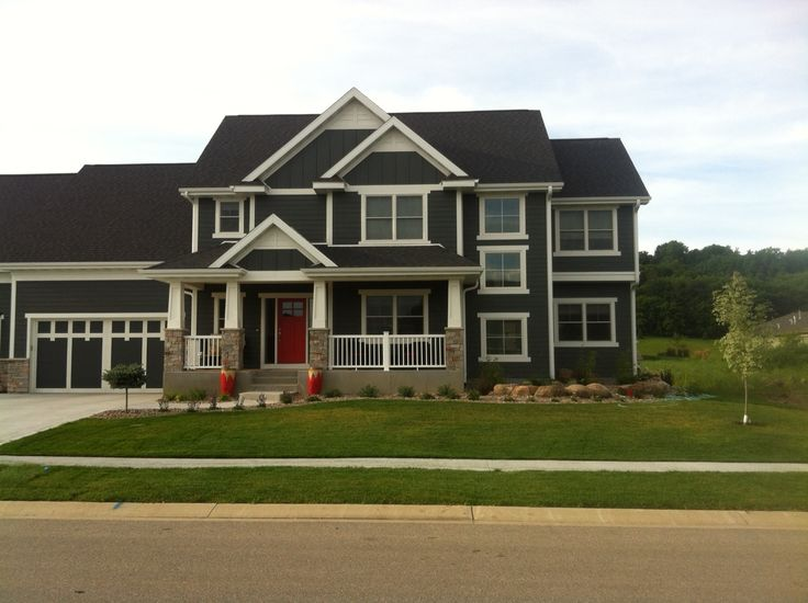 James Hardie board siding (gray), white trim, red door.  First phase of landscaping almost done.
