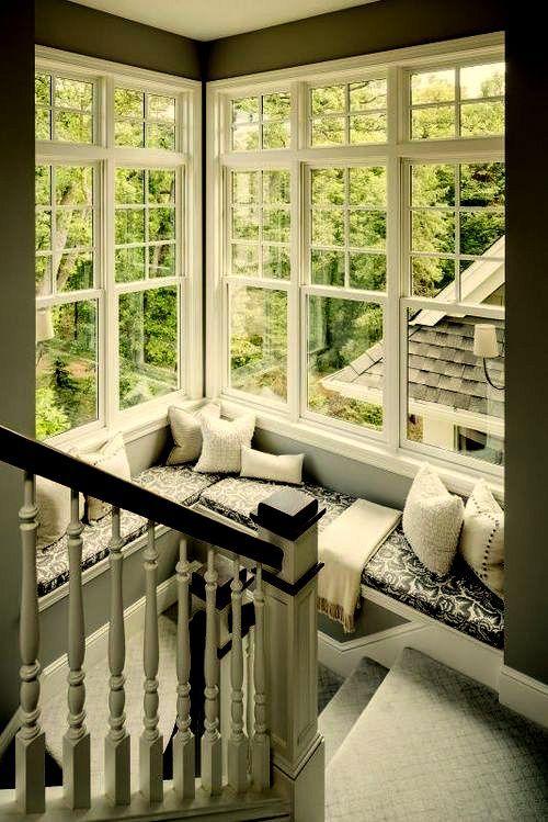 Janelas no canto da escada com um recanto para leitura.