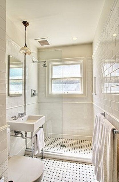 Small bathroom seems open with all white and full length shower. Minimal hardware on shower. Love... But I would add a glass shower door.