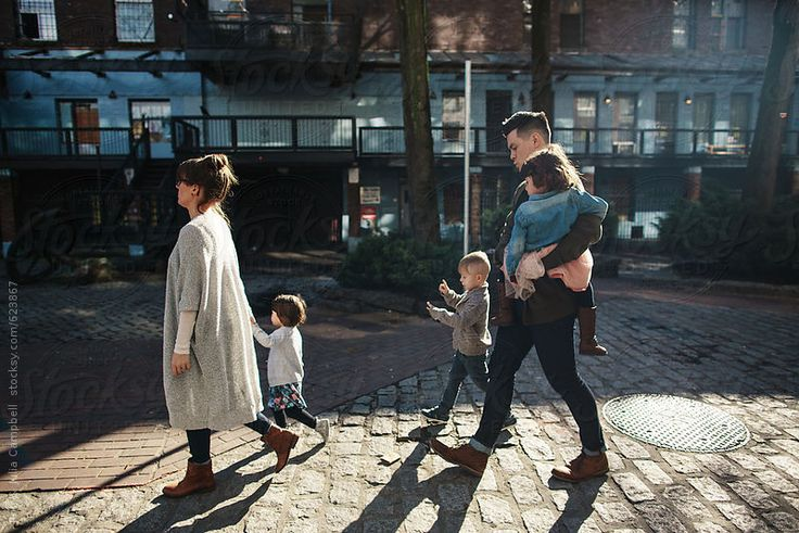 Family of five walking together in city alley way by Rob & Julia Campbell