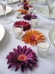 Maybe a few brightly colored crazy daisies down the center of the table to fill in around the main centerpieces.