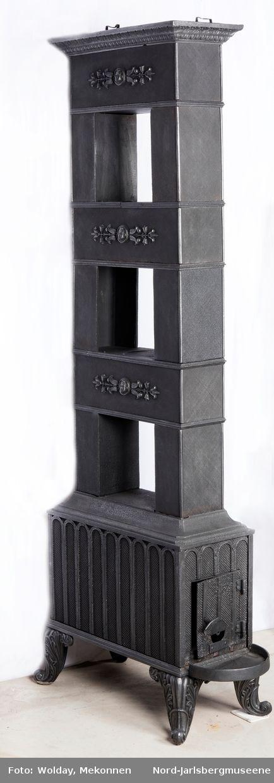 1.etasje kortside, fram: Rekatngulær stående plate med bredere sidekanter. Dør støpt med fluktuerende mønster som platen. Døra er reparert; godset er brent gjennom nederst, under rund trekkluke (uten  dør) der det nå er festet en liten plate med to klinker. Døra hengslet - festet med moderne spiker som er klinket fast og svertet?. Dørvrider med innvendig slå. Dekoren er tre søyler med bue over, hver av søuylene med hhv E 0´V preget inn (over døra). bakre kortplate lik fremre, uten dør og…