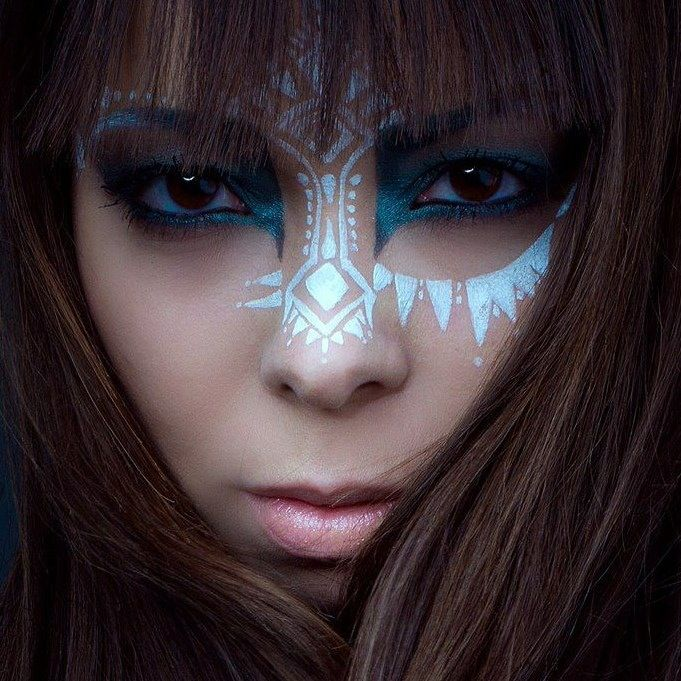 Tribal eye make-up, geometric embellishment. Striking, blue and white.