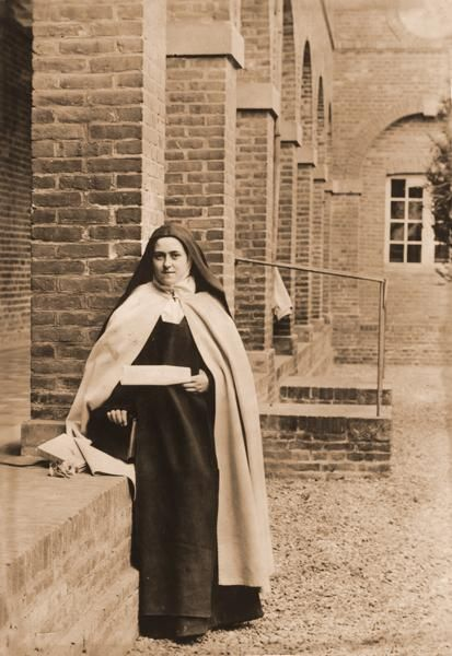 "Photograph of St. Thérèse of Lisieux taken by her sister Céline in the inner court yard of her cloister (1896). Thérèse holds a parchment on which she wrote the words of St. Teresa of Avila: ""I would give a thousand lives to save a soul."""
