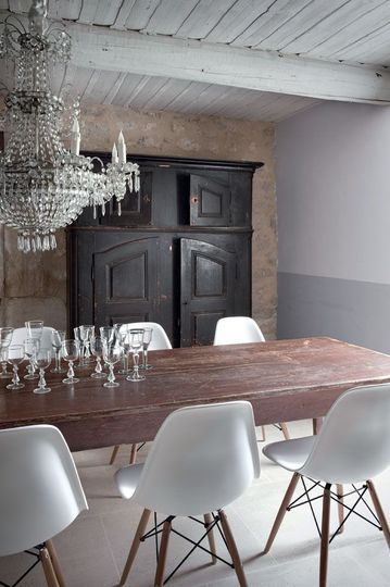 modern chairs with antique chandelier and dish cabinet