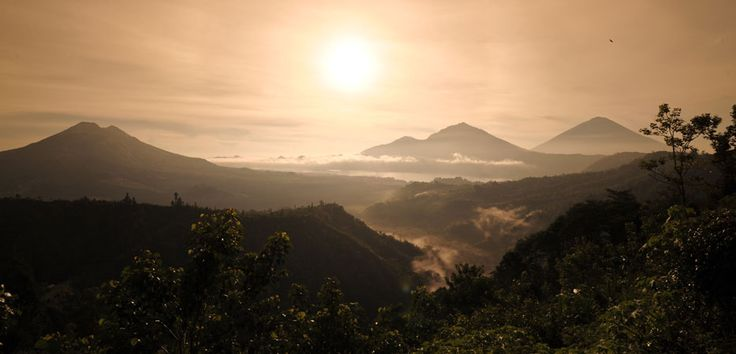 Sunrise from behind majestic Mount Batur, spraying rays onto the beautiful scenery makes for an illuminating morning smile