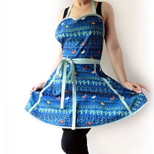 The free retro apron pattern features a sweetheart neckline, half circle skirt and finishes above the knee with contrasting bias binding and ties.