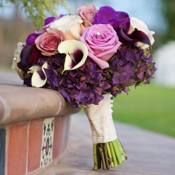 Purple hydrangeas add heft to this bold bouquet of roses and calla lilies.