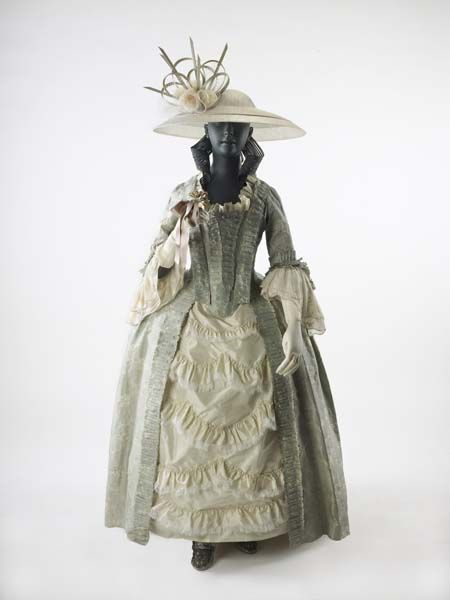 Dress Ensemble, 1760s, England, very fine silk (lustring). The small flower pattern in off-white woven into the pale blue background dates fabric to ca1755, though the gown was made possibly a decade later. Part of a trousseau. [Hat by Philip Treacy. Metal wig by Yasemen Hussein]. | Museum of London