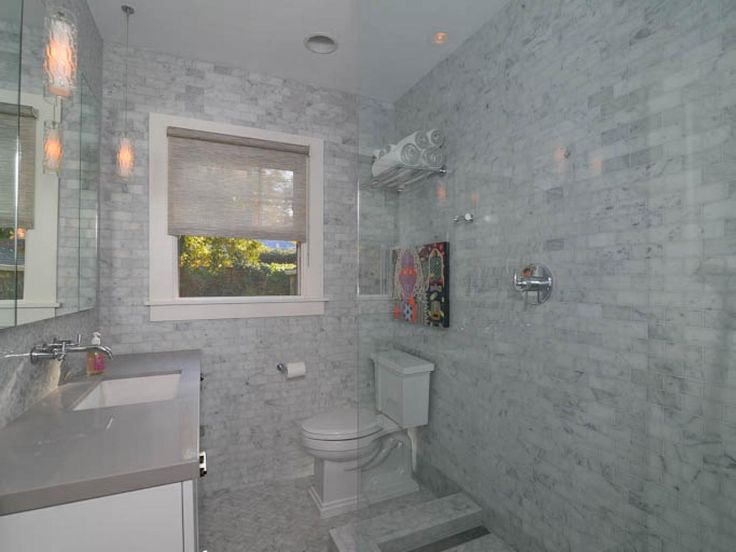 Tiled in a multitude of soft cray hues, the bathroom has an all-over contemporary vibe.