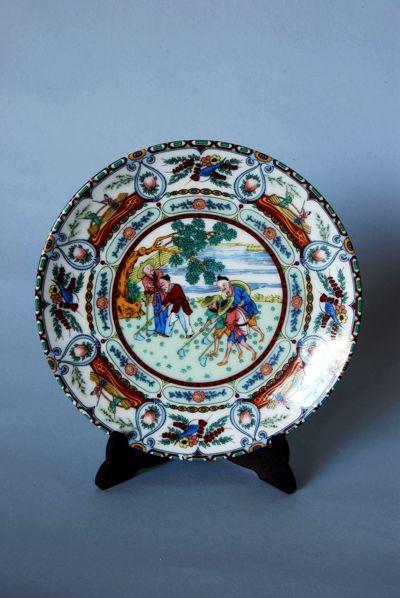 Bonito plato en cerámica de Macao con escena costumbrista central y profuso decorado.
