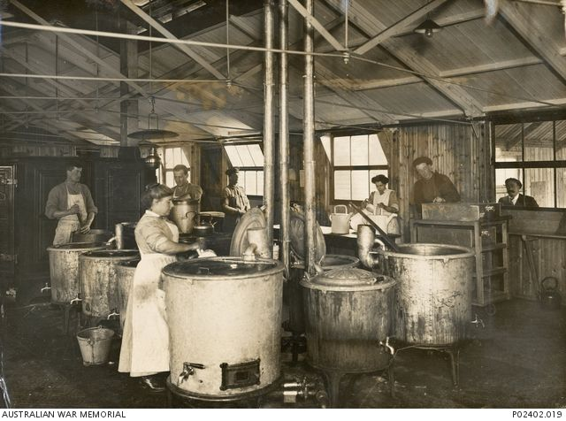 Interior of the kitchen of No. 1 Australian Auxiliary Hospital (1AAH). Two women and four men (one in uniform) work at the large vats and kettles and a trolley of food trays. In the background a ...