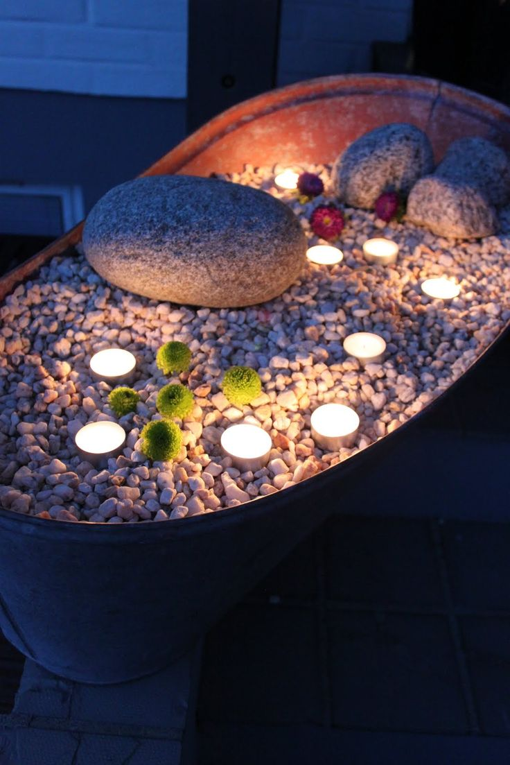 Tea lights in an old pot with stones and pebbles. Great atmosphere and light.
