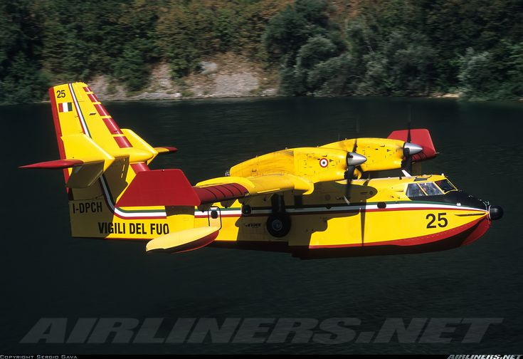 Italy - Vigili del Fuoco Canadair CL-215-6B11 CL-415 	 Off-Airport - Lago di Cavazzo Italy, August 11, 2013 . Low pass in the narrow valley over the lake aimed to warn small boats to get away from the landing path before touch down to load water. Deployed to esinguish a forest fire near the italian/Austian border.