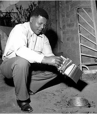 "Nelson Mandela as first Black President and South African Anti-Apartheid leader is pictured burning his ""pass"" in which blacks were required to have with them.. identifying their race and origins."