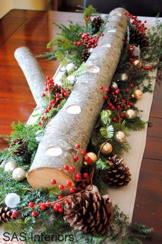 I love this pretty Christmas table runner decor, DIYed from a tree branch, candles, fairy lights, fern branches, pine cones and holly berries!