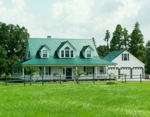Dormered farmhouse with green metal roof and wrap around for Ranch style metal homes