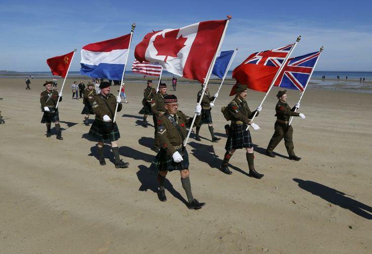 La commémoration du Débarquement en Normandie - Des amateurs d'histoire venus des Pays-Bas marchent sur Juno Beach (Calvados), zone d'atterrissage des soldats canadiens pour le D-Day, en Normandie, le 6 juin 2014.