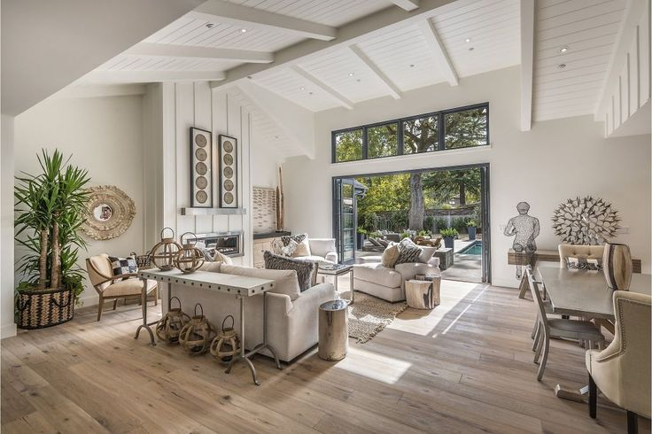 A vaulted, beamed ceiling towers above a great room with white oak flooring, a