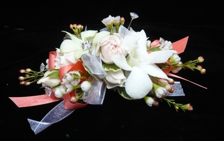 White dendrobium orchids and pale pink spray roses with waxflower on coral and silver ribbons. Another velcro wristlet for a tiny wrist. #corsage for #prom by Emil J Nagengast Florist in Albany NY