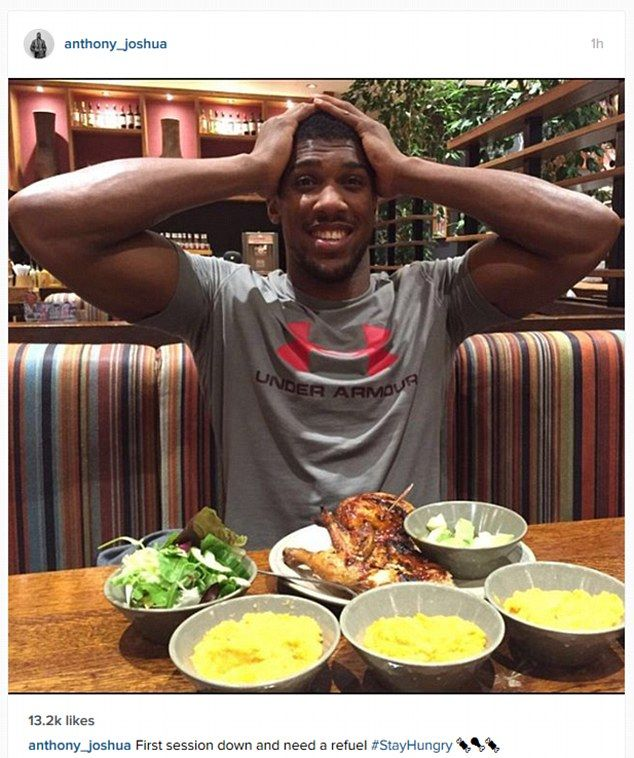Heavyweight boxer Anthony Joshua tucks into a meal at Nando's while taking a break from training