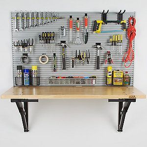 this workbench folds down flat against the wall! Perfect for tight garages, but I think my craft room would be so much more useful with one of these! Plus the board to hang all your tools....awesome!