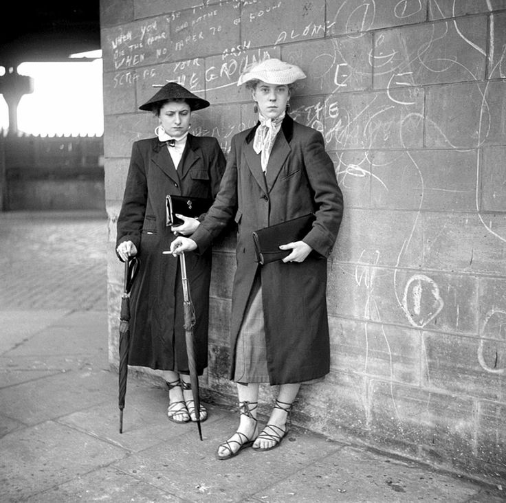 In 1955, freelance photographer Ken Russell took photos of Teddy Girls in Notting Hill. even with lower wages than the boys, Teddy girls would still dress up in their own drape jackets, rolled-up jeans, flat shoes, tailored jackets with velvet collars and put their feminine spin on the Teddy style with straw boater hats, brooches, espadrilles and elegant clutch bags.