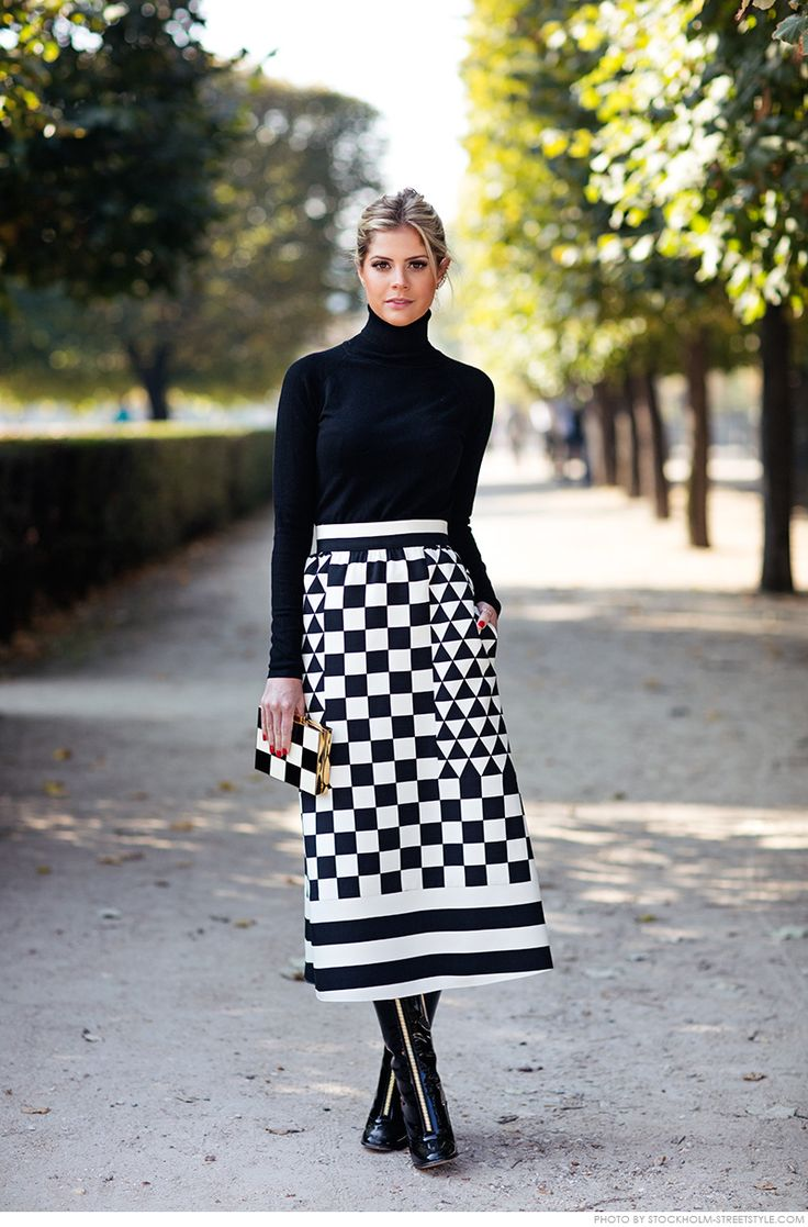 Winter outfit: black turtleneck, black-white graphic midi skirt, black boots, checkboard clutch: