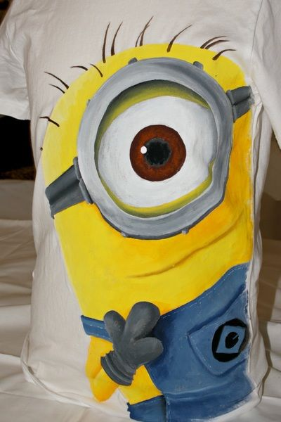 """Hand painted boy's t shirt, featuring a Minion, from the movie """"Despicable Me"""". The colors are non-toxic, water based, permanent fabric colors."""