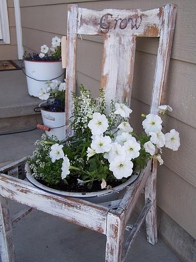 white flowers in bucket in seat old chair on porch, simple vintage garden styling Repinned by www.silver-and-grey.com