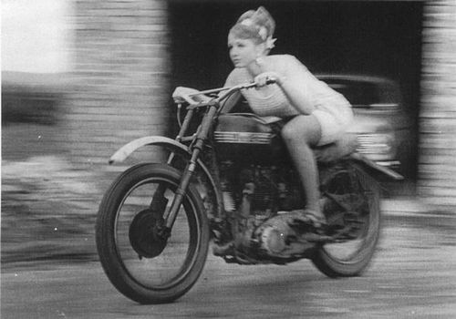 Best guess is that she's on a stripped down, early 1950s Triumph Thunderbird. Possibly photographed in England.