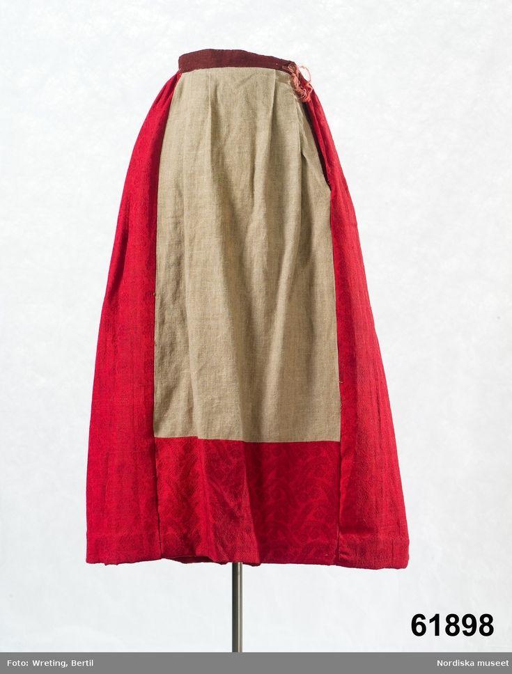 Kjol i rött ylle av kamgarn med invävt blommönster, 6 våder, framvåden som dolts under förklädet består till övre delen av oblekt linnelärft och har upptill 4 lagda veck och ett sprund.  Östra härad.