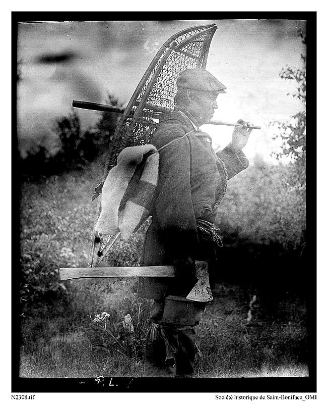 A Dene Metis from La Loche, Saskatchewan, 1920: Boniface Janvier is wearing a metis sash with the ends tucked in and metis garters tied just below the knees. He is carrying a rifle, snowshoes, an HBC blanket, an axe and a kettle. He is possibly heading north of the Clearwater River to a cabin on his trap line for the winter.