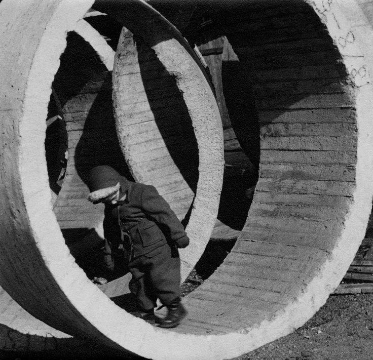 Poika leikkii rakennustyömaan betonisissa kaivonrenkaissa. Kuva Elanto -lehden kokoelmasta. 1950 -luku. Lähde: HKM (CC BY-ND 4.0).