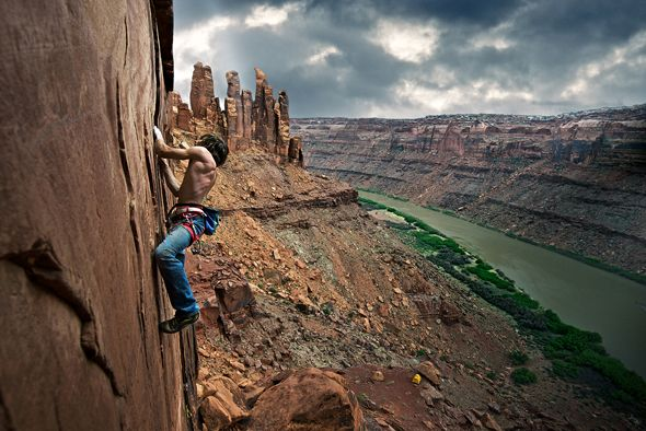 Daniel Woods climbing High Deductible, 5.12, in Labyrinth Canyon, Utah, with the Green River below; Photograph by Celin Serbo