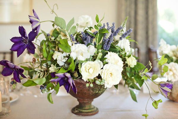 Purple green white centerpiece in a rustic urn vase