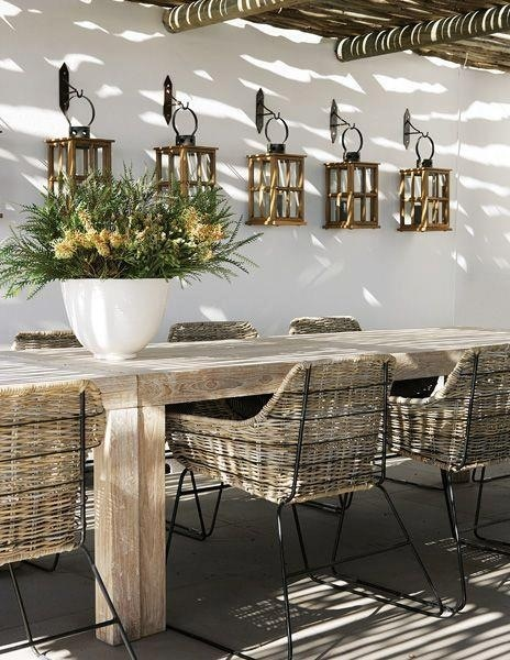 Outdoor dining. Pergola wood table. Lanterns hanging on wall.