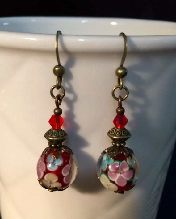 Vintage style dangle earrings with glass lampwork, and crystal beads. In bronze and red with cute flowers on beads. $9