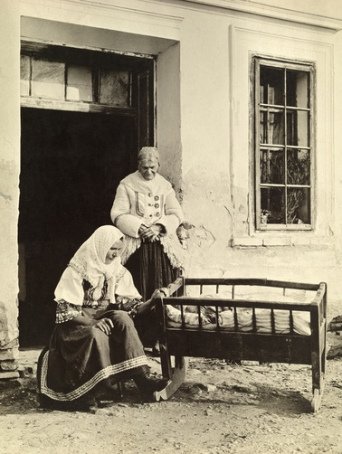 Picture Id: 938075  A Slovak mother rocks her child in a cradle outside their home. Location: Bohemia.  Photographer: A. W. CUTLER/ National Geographic Stock