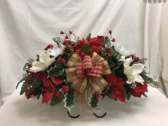 This Christmas arrangement is made with Red Poinsettias, White Magnolia , Ribbon, Christmas Holiday cemetery saddle. Holiday Christmas Silk Flower Cemetery, Cemetery Saddle, Tombstone Saddle ,Cemetery flowers , Grave flowers.  Cherish the memories of your loved one with one of our Cemetery Tombstone/Headstone Saddle Arrangements of Poinsettias and Christmas Accents . It is an elegant way to honor your loved one. The 37 inches long, 18 inches wide arrangement can be fitted to any sized…
