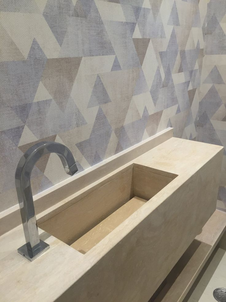 Lavabo com cuba esculpida em marmore. Papel de parede vinilico usado para dar mais modernidade ao ambiente.