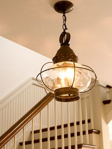 Light fixtures reminiscent of a bygone era give this newer house character. The reproduction cast-iron light in the foyer is similar to a boat lantern.