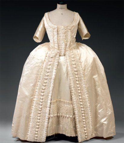 Robe à la française, Provinces-Unies (?), vers 1760-1770. Satin de soie ivoire ; modèle à plis plat dans le dos, coulissé sur les paniers, manches mi-longues incomplètes, le buste fermé par une sorte de pièce d'estomac cousue à un coté du manteau