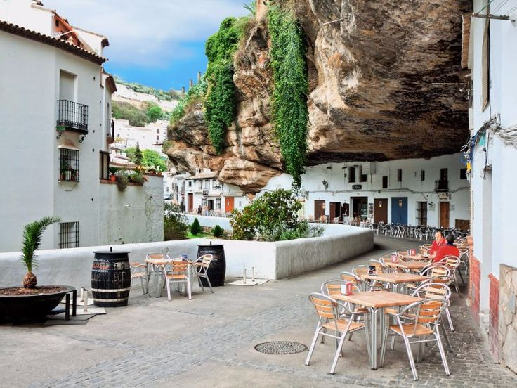 Setenil de las Bodegas grew out of a network of caves located in the cliffs above the Rio Trejo in Spain. Today, its white houses have been built within this network, and some even have rock roofs. The area is also home to bars, restaurants, and spectacular food.