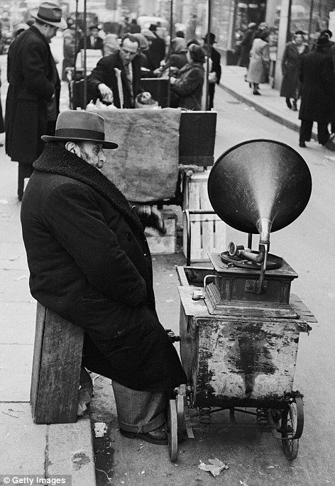 A man with a gramophone on wheels at a street market in Whitechapel in April 1952