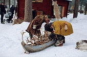 Men in traditional clothing look at a pulk (sled) at the traditional Sami Market, Jokkmokk. Sweden.