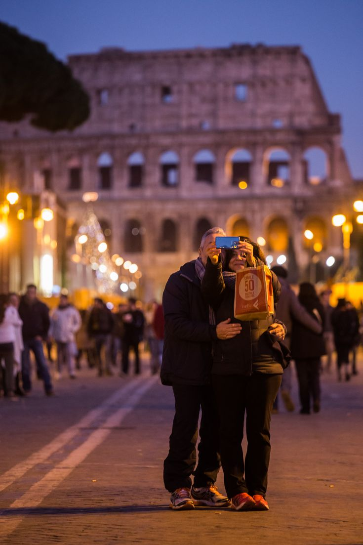Tourist couple taking a selfie at the Colosseum at blue hour